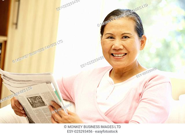 Senior Asian woman reading newspaper