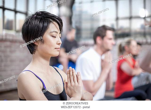 Young woman doing yoga meditaiton exercise in studio