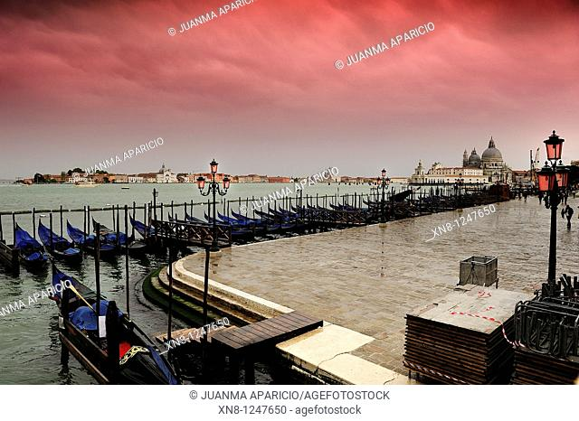 View of the Grand Canal with a row of moored gondolas on a cloudy day with mauve gradient filter in the sky, Venice, Italy