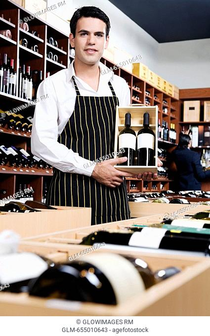 Sales clerk holding a crate of wine bottles