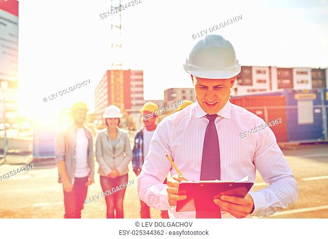 business, building, teamwork and people concept - group of smiling builders and architect with clipboard in hardhats at construction site