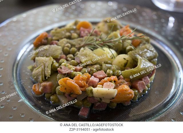 Plate with hot salad of vegetables with serrano ham Spain