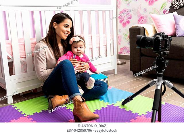 Profile view of a young Hispanic mother and her baby recording a video for her parenting blog