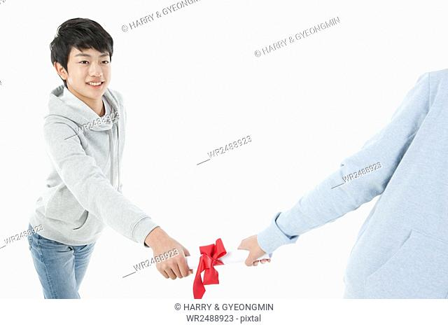 Smiling school boy in casual clothes taking a baton of certification from one school boy