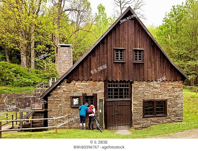 two people looking into the old ironworks and hammer mill Wendener Huette, Germany, North Rhine-Westphalia, Sauerland, Wenden-Huensborn