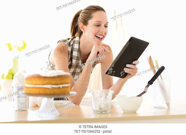 Woman using tablet pc in kitchen