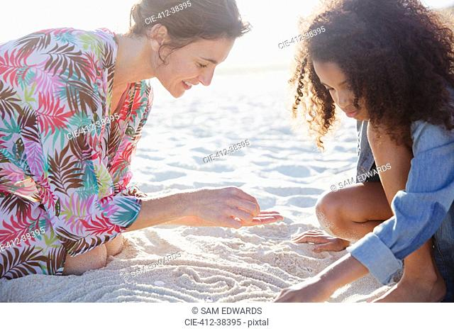 Mother and daughter drawing in sand on sunny summer beach