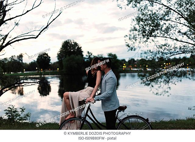 Romantic young couple on bicycle gazing at each other by lake at dusk