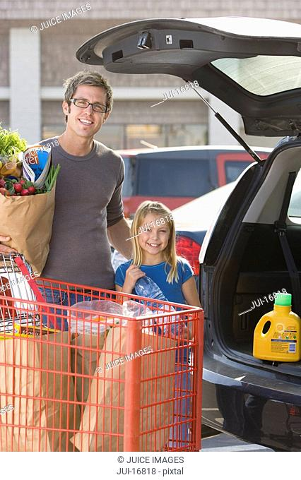 Father and daughter loading grocery bags in car