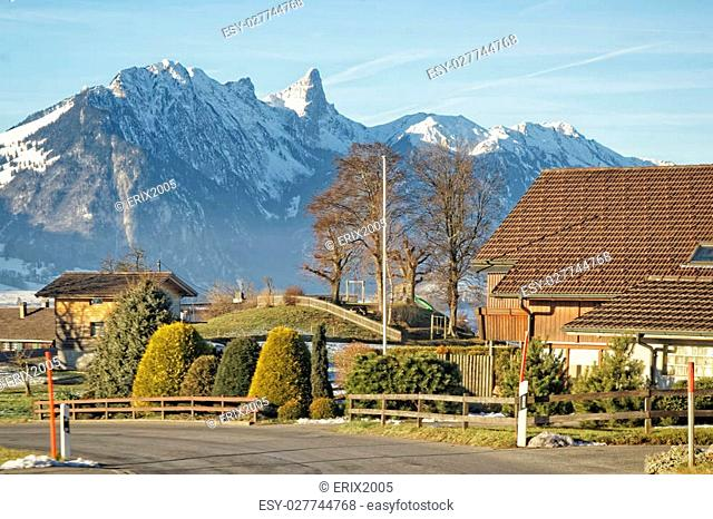A village with a view to the Swiss Alps mountains near the Thun lake in winter