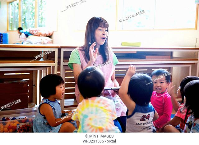Female teacher telling story to group of children in a Japanese preschool