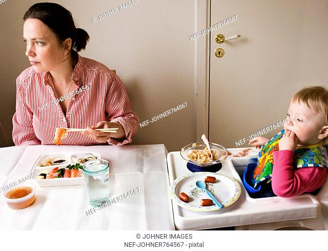 Mother and baby daughter having dinner, Sweden