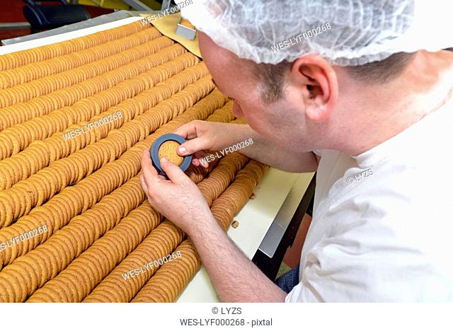 Germany, Saxony-Anhalt, man controlling quality of cookies with a stencil in a baking factory