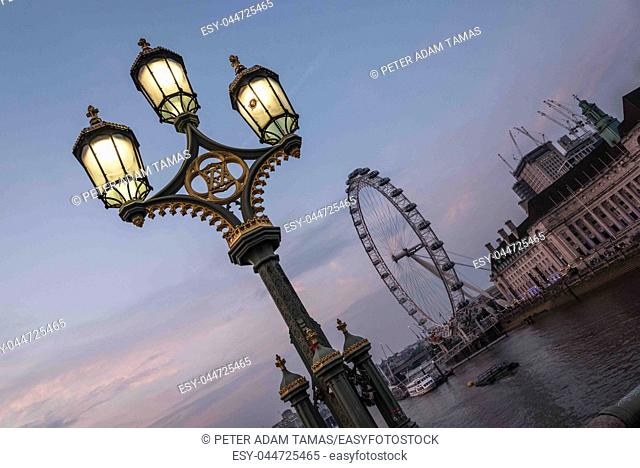 View of the London Eye with the City Hall of London from the Westminster bridge with a nice street light after sunset