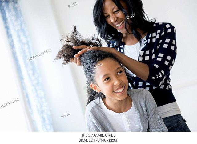 Mother styling hair of daughter