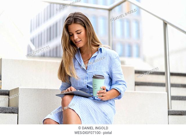 Portrait of young businesswoman using tablet, with coffee to go cup