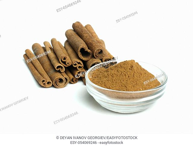 Powdered cinnamon in bowl and cinnamon sticks on white background