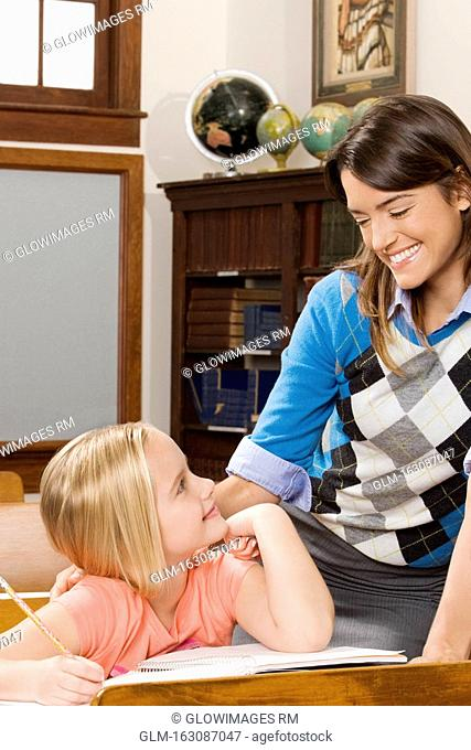 Schoolgirl and her teacher smiling in a classroom