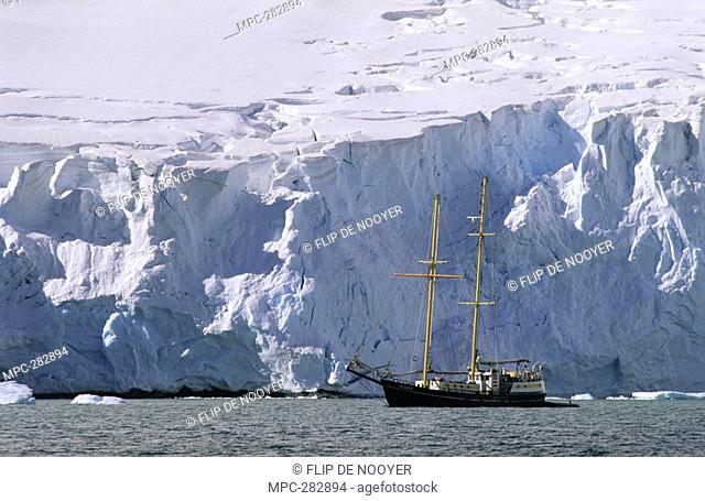 Sailboat dwarfed by glacier, Lemaire Channel, Antarctica