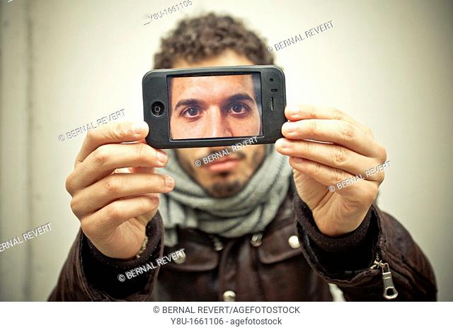 A young man takes a picture with an iPhone
