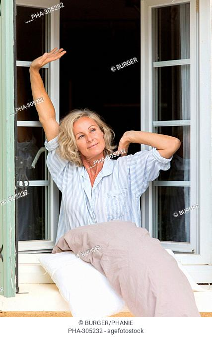 Woman stretching arms by the window