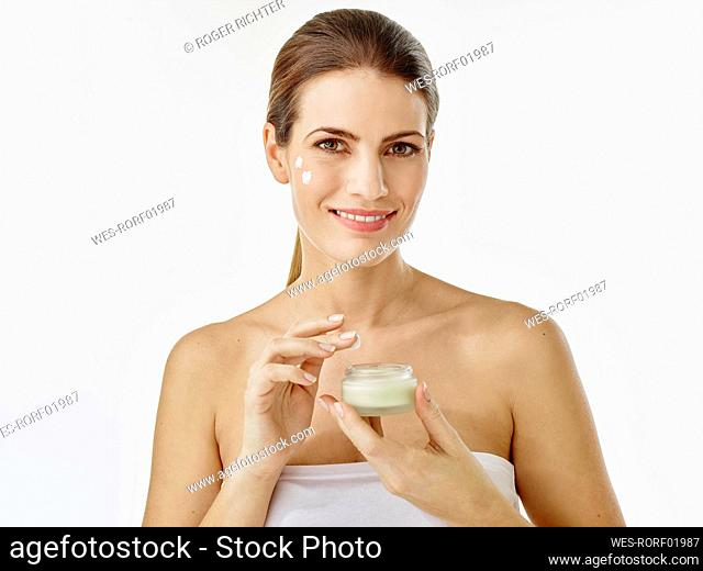 Portrait of smiling woman with cream jar