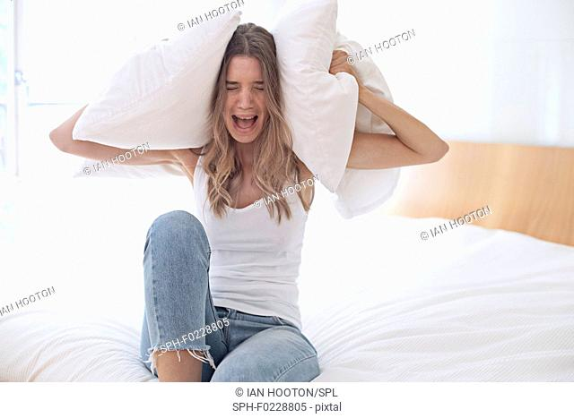 Young woman holding pillow over her ears and screaming