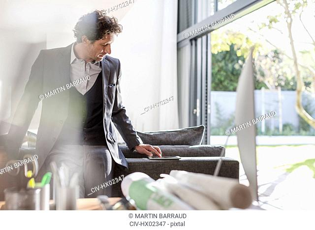Male architect using digital tablet in home office