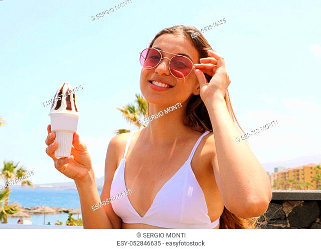 Portrait of girl with sunglasses holding ice cream on the beach