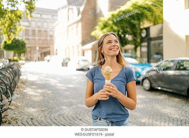 Netherlands, Maastricht, smiling blond young woman holding ice cream cone in the city
