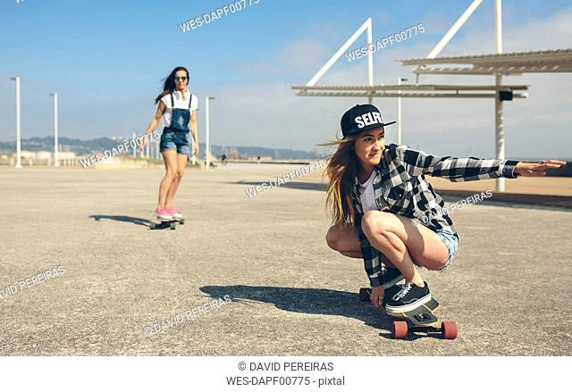 Two young women longboarding on beach promenade