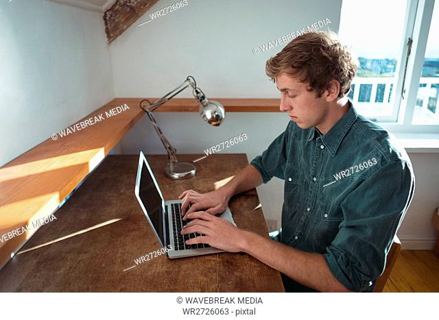 Man sitting at desk and using laptop