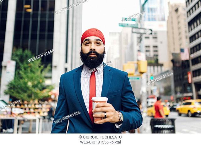 Indian businessman walking in Manhattan, drinking coffee