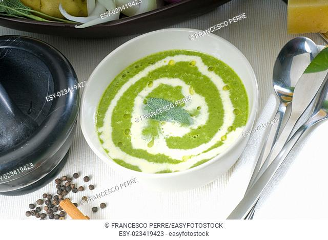 fresh spinach soup on a white bowl with sage and cream on top