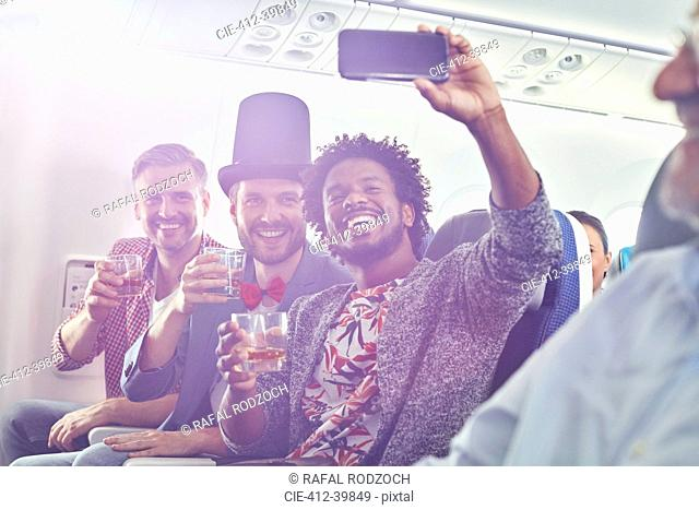 Enthusiastic young male friends with camera phone drinking and taking selfie on airplane