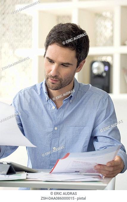 Man looking through monthly bills