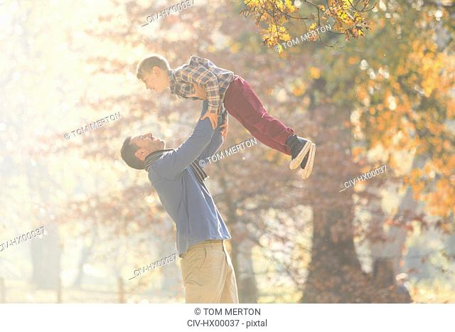 Father lifting son overhead in woods with autumn leaves