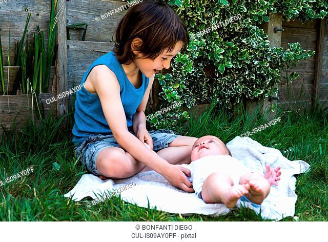 Boy tickling baby brother in garden