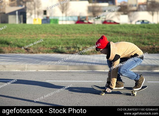 Male skateboarder riding and practicing skateboard in city outdoors