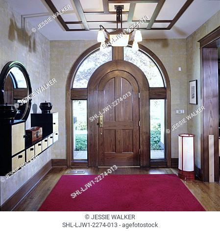 entry ways: arts and craft home, view towards arched outside door, woodfloor with red area rug oriental art deco shelving and mirror on wall