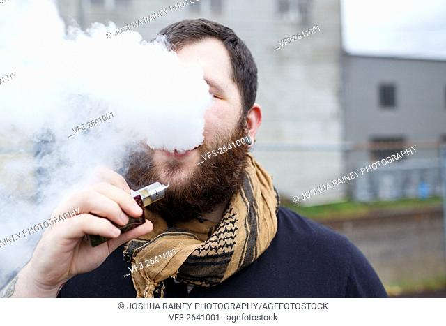 Urban lifestyle portrait of a man vaping in an urban environment with a custom vape mod device