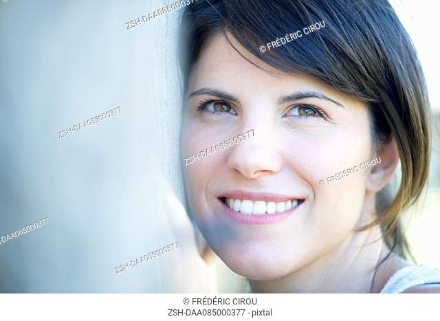 Woman resting head on tree trunk, smiling cheerfully