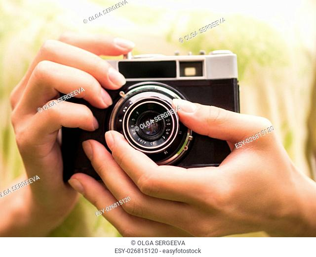 Close up girl holding retro camera and taking photo
