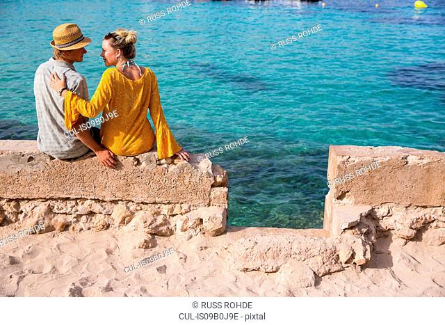 Rear view of couple sitting on wall by sea, Majorca, Spain