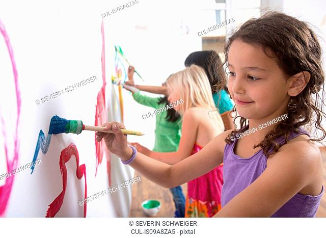 Group of girls painting wall