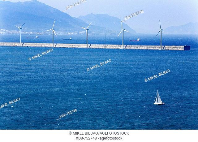 sailboat sailing in the Abra, and breakwater with wind turbines, near Bilbao  Biscay  Biscayan coast  Basque Country  Spain