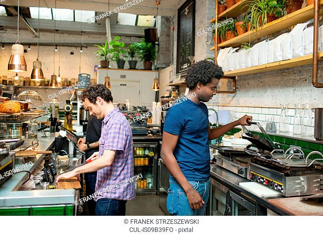 Two waiters preparing food in cafe kitchen