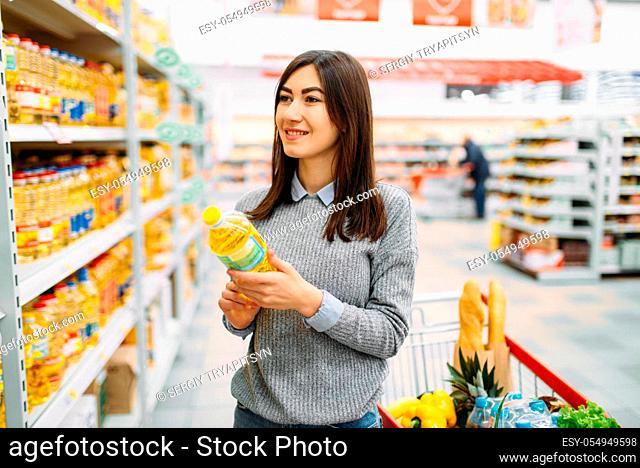 Woman choosing sunflower oil in a supermarket, family shopping. Female customer in shop, buyer in market