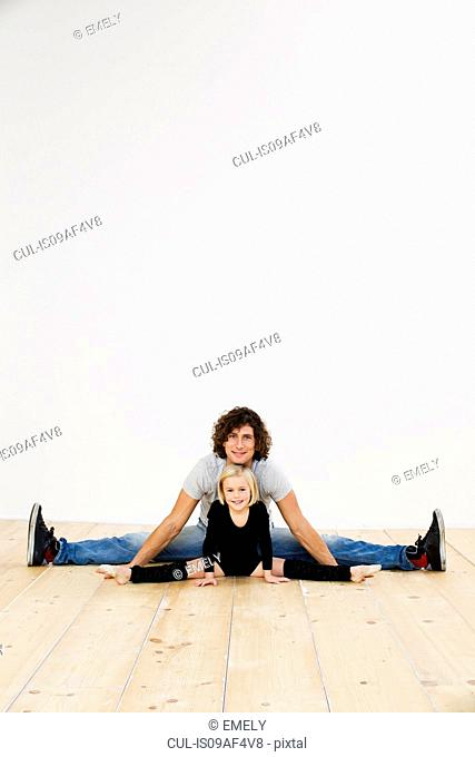 Studio portrait of father and ballerina daughter doing splits