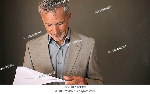 A senior businessman smiling while making and then throwing a paper plane